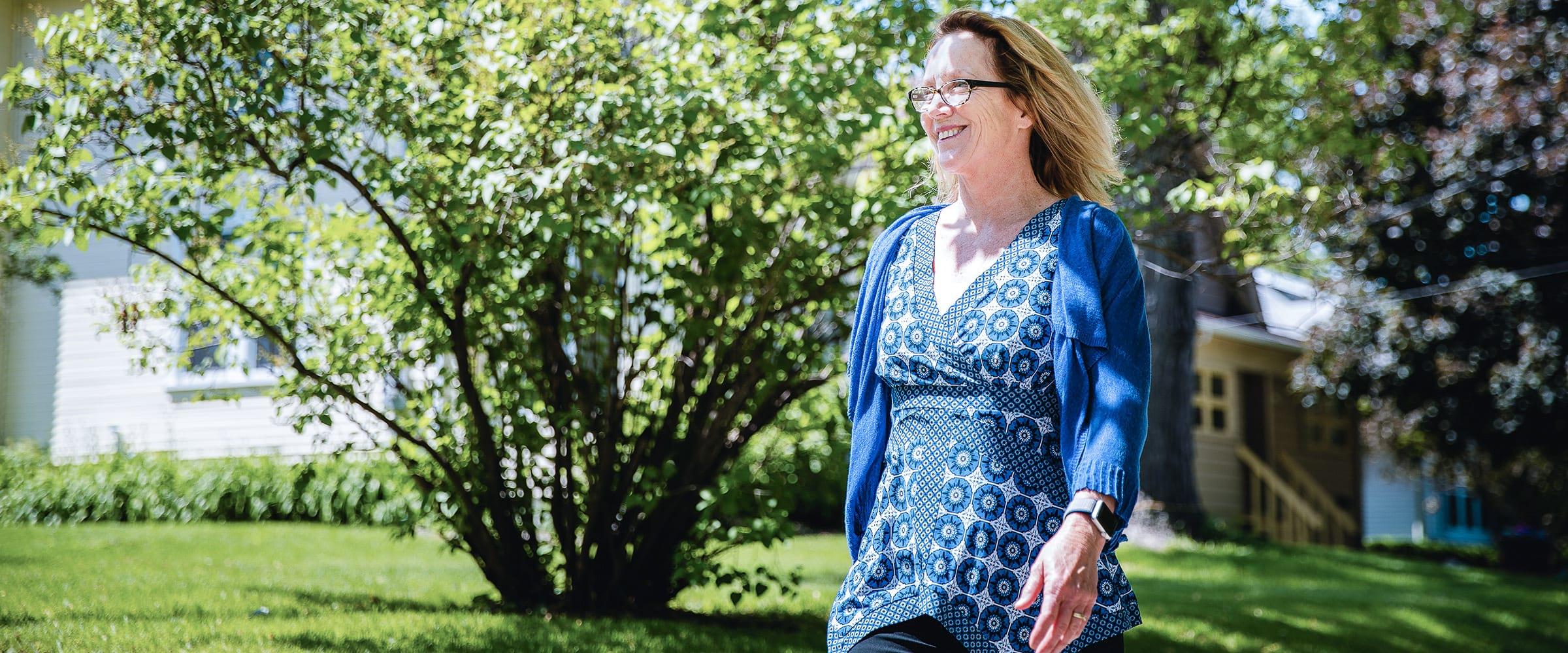 A woman in a blue dress walking outside