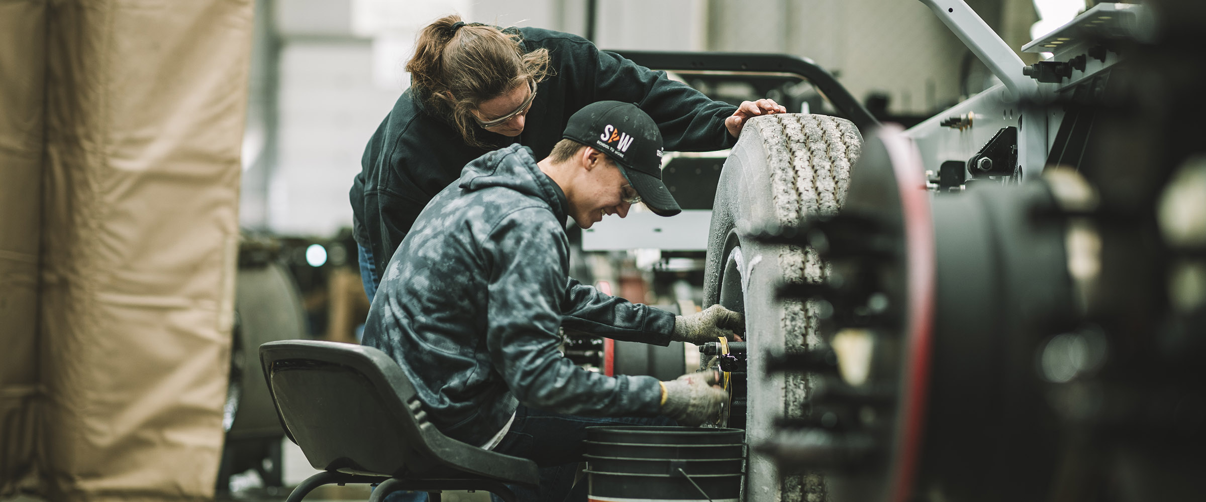 High school student and production worker working on a truck tire
