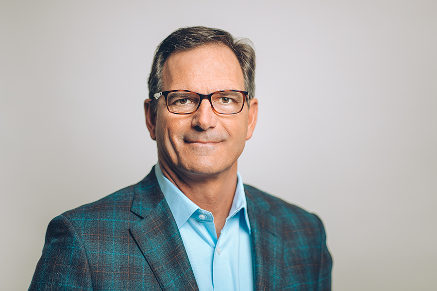 Head shot of CEO, Wilson Jones, in a blue shirt and checker patterned jacket wearing glasses