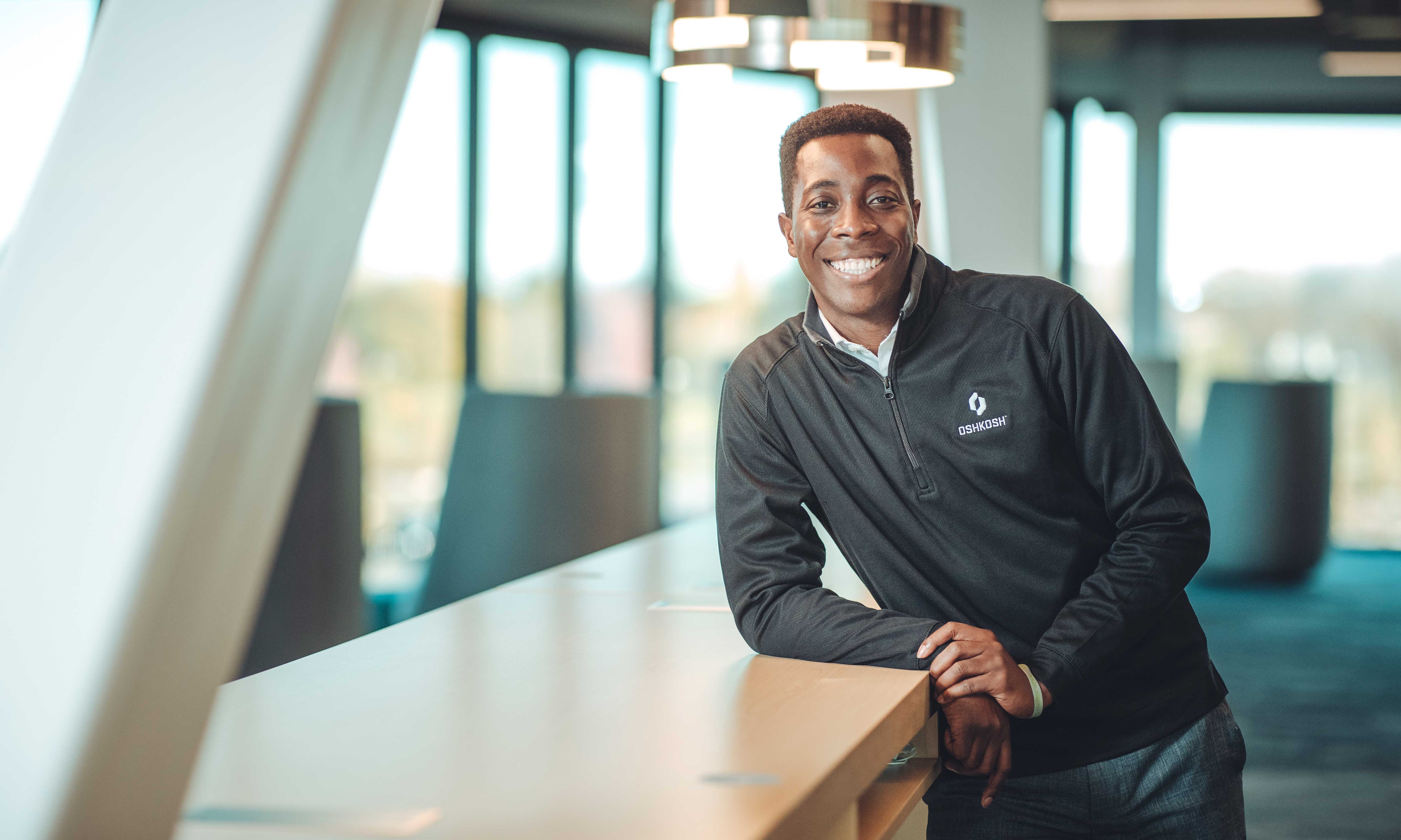 Young black man wearing a black Oshkosh 1/4 zip sweatshirt standing at a tall table in an office setting